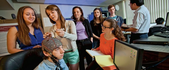 In the Brain-Computer Interface Lab. Camila Moscoso '16 (L-R) and Maura Schlussel '15 adjust electrodes on cap worn by Brandon Smith '17 that records brainwaves. Looking on are Alexandria Battison '16 (foreground) and Prof. Lisa Gabel (L-R), Alexandra McCullough '16, Tom Fuller '16, and Prof. Yih-Choung Yu.