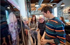 Leslie Tintle '16 (L-R), Prof. Kerns, Ben Williamson '16, and Allison Reich '15 review artwork.