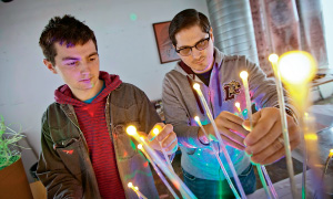 Ben Williamson '16 (left) and Scott Kovacs, a  part-time student, adjust lights and wiring for one  of the venue sets.