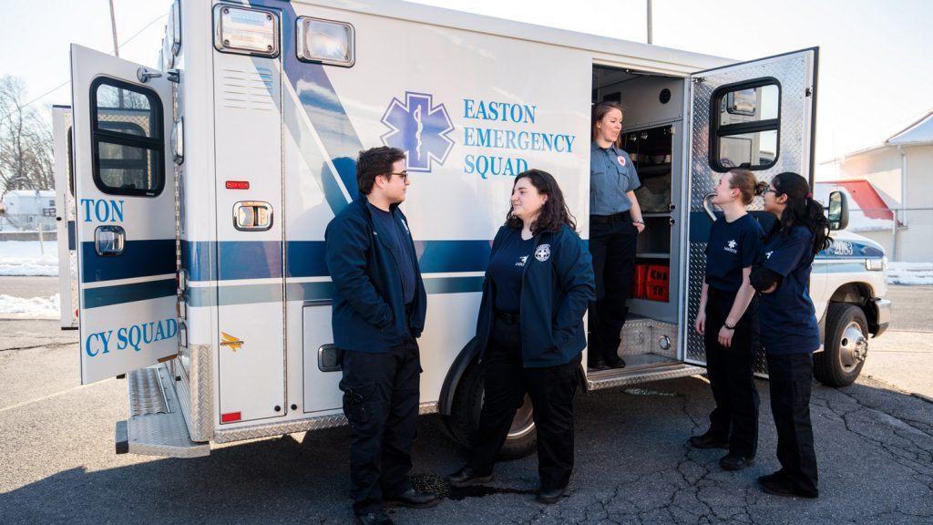 Student emergency medical technicians talk by an Easton Emergency Squad ambulance.