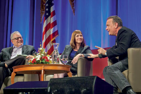 President Alison Byerly smiles as Tom Hanks talks on stage, Donald Miller sits with her