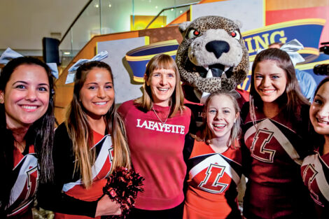 Lafayette College President Alison Byerly wears a College sweatshirt and smiles with cheerleaders and the Leopard mascot