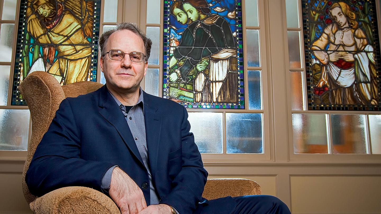 Eric Ziolkowski sits with stained glass artwork behind him