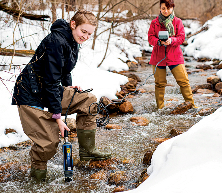 Lafayette College biology student Nikki Morley uses a water testing device with Megan Rothenberger in an outdoor stream