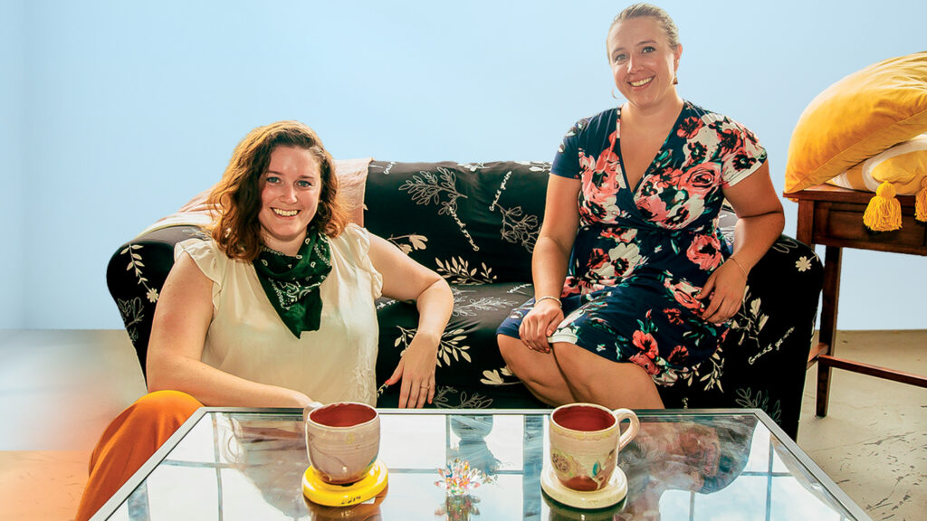 April Hinkle and Caitlin Flood '12 sit in a living room they furnished
