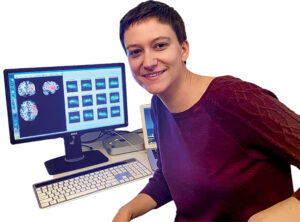 Meghan Caulfield sits at a desk with a computer with brain scans on the screen
