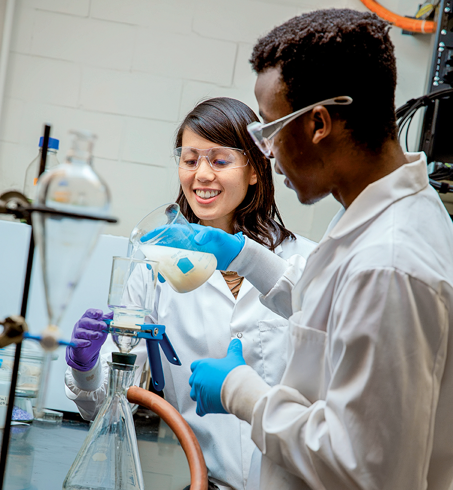 Lindsay Soh wears goggles, gloves, white lab coat in the lab with a student