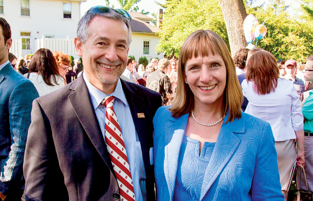 Alison Byerly and her husband, Steve Jensen, smile together as they host a post-Commencement celebration for students and families at their house.